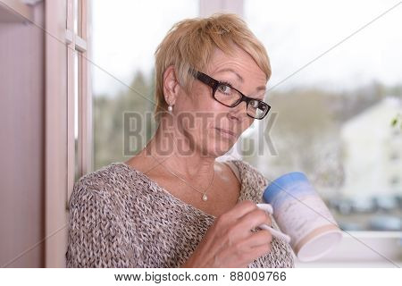 Serious Blond Woman With Glasses Holding A Cup