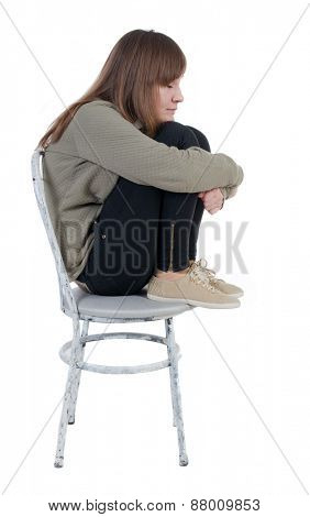 Lonely, closed woman sitting on chair. Isolated over white background.