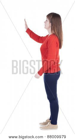 back view of woman. Young woman presses down on something. Isolated over white background. Rear view people collection. backside view of person. she holds his hand open, palm forward