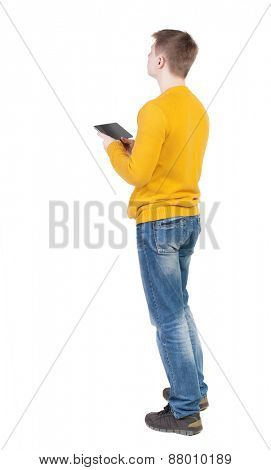 Back view of man with tablet. Standing young guy. Rear view people collection.  backside view of person.  Isolated over white background.