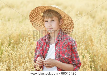 Portrait Of Teenage Farm Boy Wearing Red Checkered Shirt And Yellow Wide-brimmed Natural Straw Hat