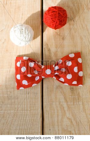 Tie Fabric With Red Polka Dots And Two Bright Balls Of Yarn Lying On A Light Wooden Background