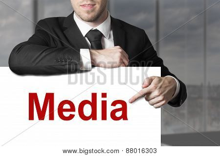 Businessman Pointing On Sign Media