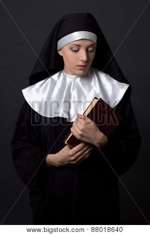 Young Woman In Nun Veil With Book Over Grey