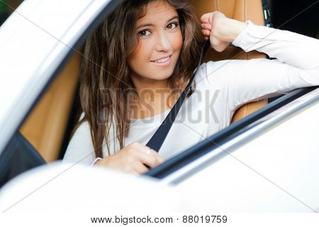 Beautiful young woman driving her car