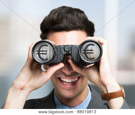 Smiling businessman looking to a Euro symbol through binoculars