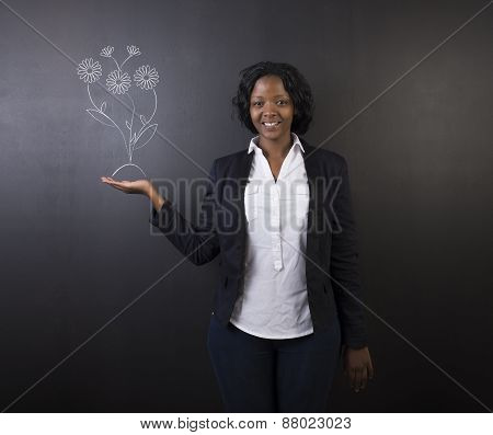 South African Or African American Woman Teacher Or Student Against Blackboard Growing Flowers