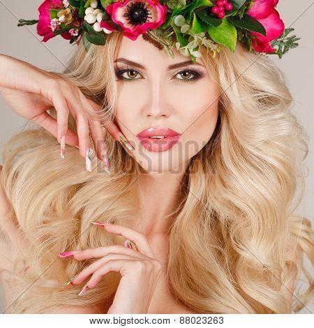 Portrait of a beautiful woman in a wreath of flowers.