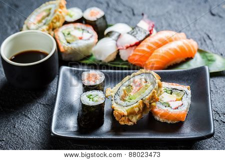Fresh Sushi Rolls On The Black Ceramic Dish