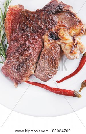 meat food : grilled beef steak on white plate with red thin pepper , spices and rosemary isolated over white background