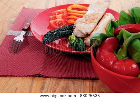fresh roast turkey meat fillet steak on red plate with tomatoes pepper green kale and lettuce salad over wooden table