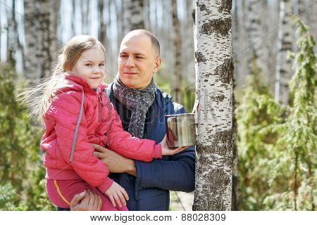 family to wood collecting birch sap in mug