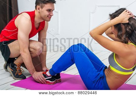 Man helping a woman or girl in making abdominal crunch, exercises concept training exercising workou