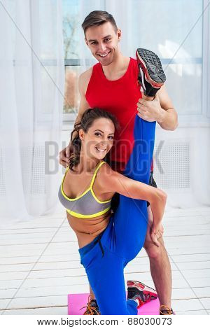 Young woman doing streching exercises with man smiling looking at camera concept training exercising