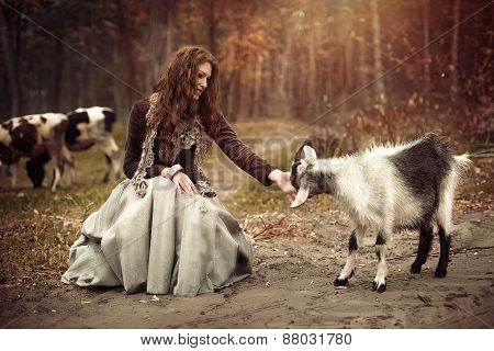 Beautiful young girl in autumn forest with goats