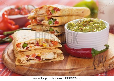 Mexican quesadillas, cheese, meat and vegetable stuffed tortilla with guacamole dip