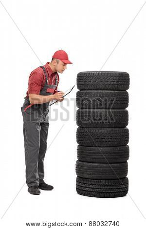 Full length portrait of a young mechanic checking the quality of a set of tires and writing down notes on a clipboard isolated on white background