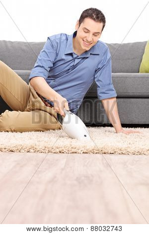 Vertical shot of a young cheerful man cleaning a carpet with a handheld vacuum cleaner in  front of a gray sofa isolated on white background