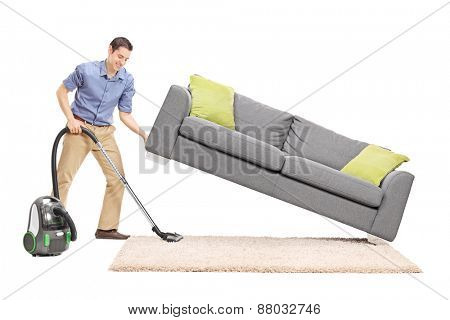 Cheerful young man lifting a sofa and cleaning underneath it with vacuum cleaner isolated on white background
