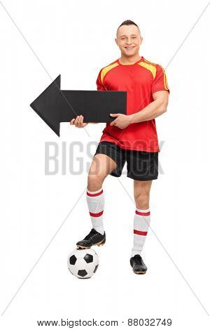 Full length portrait of a young male football player in a red jersey, holding an arrow pointing left and standing over a ball isolated on white background