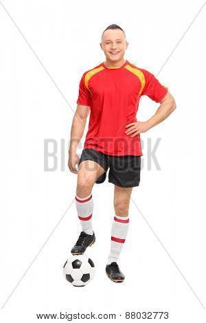 Full length portrait of a young male soccer player standing over a ball and looking at the camera isolated on white background