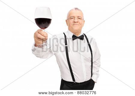 Elegant senior gentleman proposing a toast with a glass of red wine and looking at the camera isolated on white background