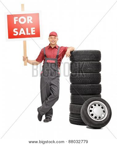 Full length portrait of a cheerful male mechanic standing by a pile of tires and holding a big red for sale sign isolated on white background