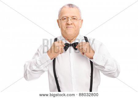 Studio shot of an elegant senior gentleman adjusting his bow-tie isolated on white background
