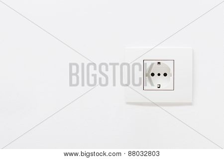 Empty white electric socket on a plain white wall