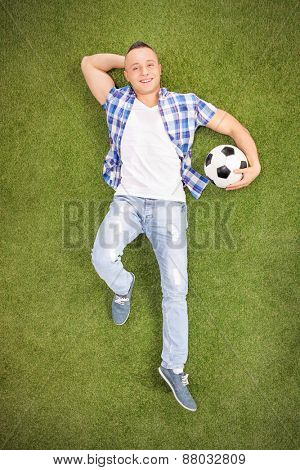 Vertical shot of a casual young man lying on a grass field, holding a football and looking at the camera