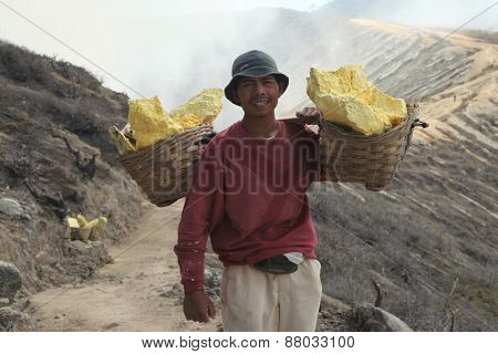 KAWAH IJEN, INDONESIA - AUGUST 10, 2011: Miner carries baskets with sulphur in fumes of toxic volcanic gas from sulphur mines in the crater of the active volcano of Kawah Ijen, East Java, Indonesia.