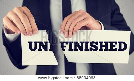 Businessman Tearing A Small White Paper With Unfinished Word
