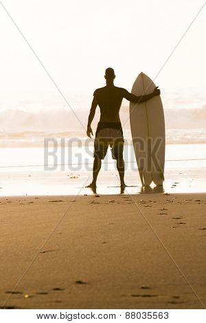 Silhouette of a surfer man at the beach with his surfboard