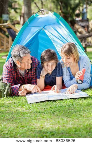 Happy family with son reading map in tent at park