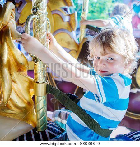 Little Cute Child During Carousel Ride, Enjoying And Having Fun