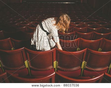 Woman Taking Her Seat In Auditorium