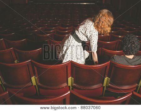 Woman Taking Her Seat Next To Man In Auditorium