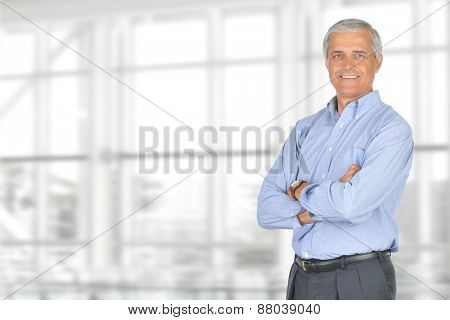 A smiling casually dressed mature businessman standing in front of a large modern office window. The man is set ot the right of the frame leaving room for your copy. Horizontal format.
