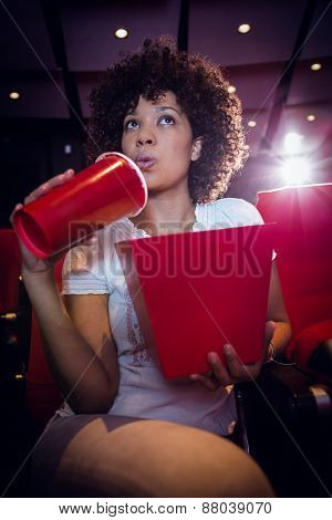 Young woman watching a film and drinking a soda at the cinema