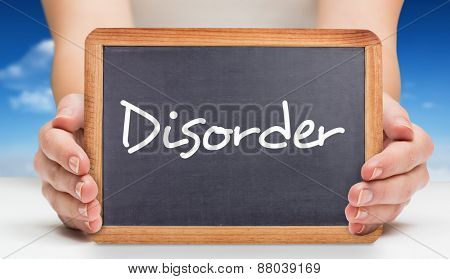 The word disorder and females hands showing black board against bright blue sky with clouds