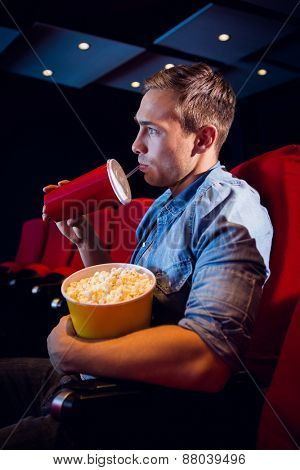 Young man watching a film at the cinema