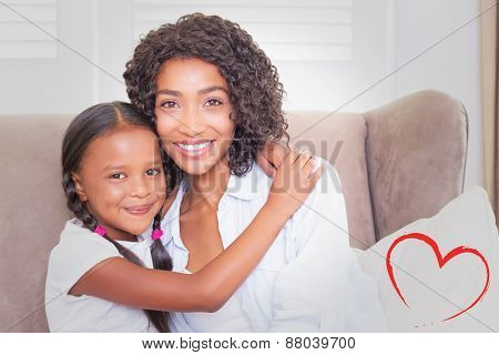 Heart against pretty mother sitting on the couch with her daughter smiling at camera