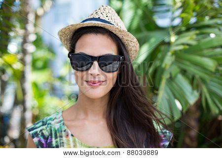 Smiling beautiful brunette wearing straw hat and sun glasses with palm tree behind her