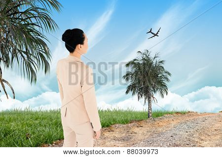Unsmiling asian businesswoman against road leading out to the horizon