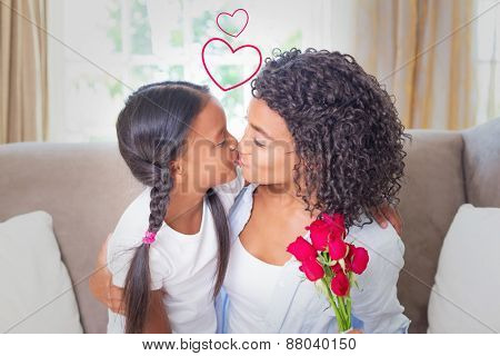 Heart against pretty mother sitting on the couch kissing her daughter holding roses