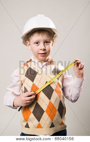 Boy In Construction Helmet And A Tape Measure In Hand