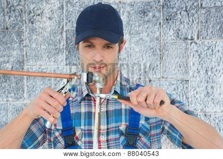 Plumber fixing pipe over white background against grey