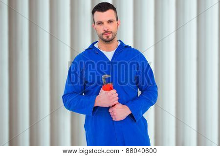 Smiling male mechanic holding monkey wrench against grey shutters