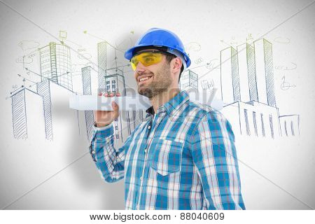 Smiling architect looking away while holding blueprint against grey