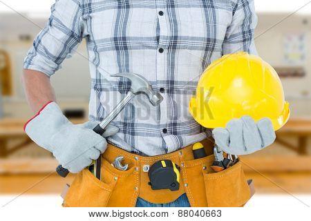 Handyman holding hammer and hard hat against workshop